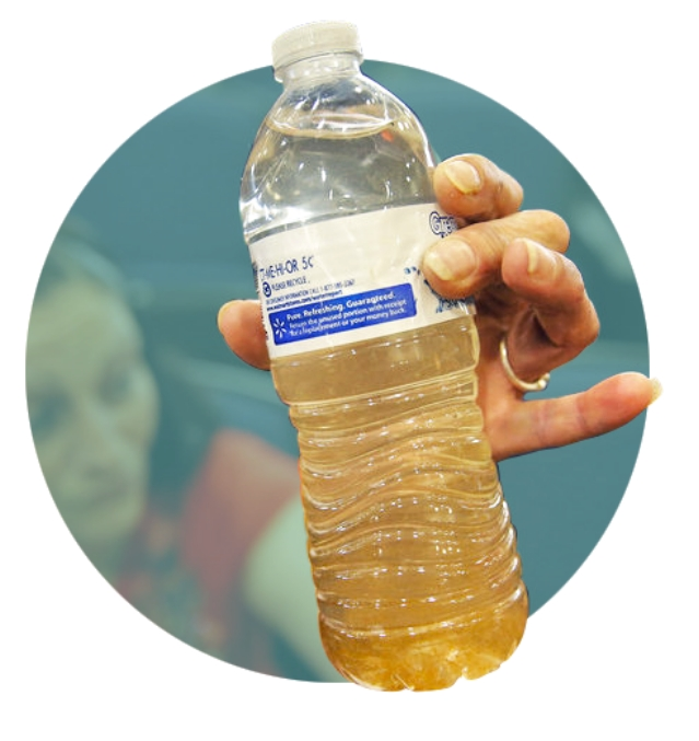 woman holding plastic bottle filled with contaminated water