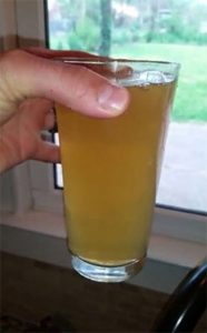 Person holding a glass of contaminated water from Mint Hill, NC